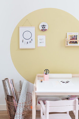 Desk and rolls of paper in basket below large yellow circle on wall