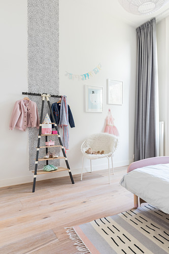Clothes rack and chair in girl's bedroom with pale grey accents