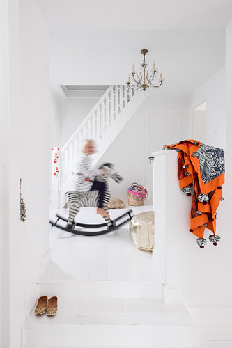 Child on rocking horse in white stairwell