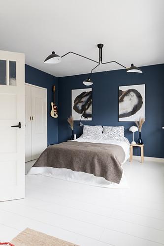 Doppelbett im Schlafzimmer mit blauer Tapete, großformatigen Kunstwerken und weißer Dielenboden