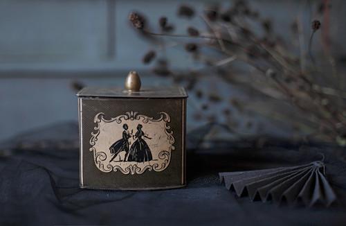 Teedose mit Scherenschnittmotiv auf schwarzem Stoff