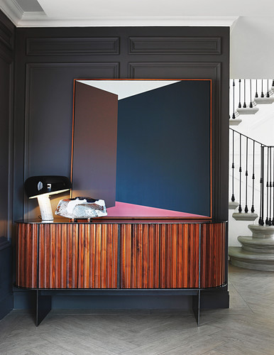 Graphic artwork on striped wooden sideboard