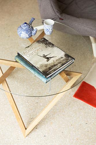 Bildband, Teekanne und Tasse auf Beistelltisch aus Glas und Holz