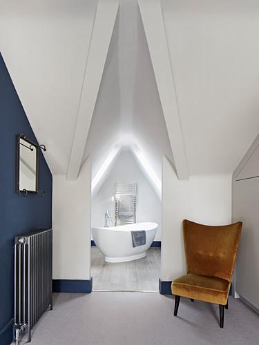 Retro armchair in front of open doorway leading into attic bathroom