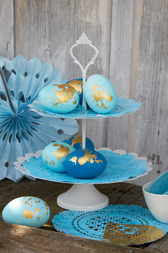 Blue Easter eggs decorated with gold leaf on cake stand