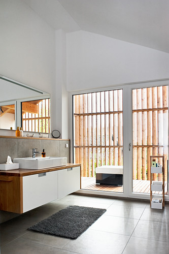 Modern bathroom with high ceiling and glass wall leading to balcony