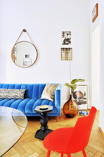 Glastisch, roter Stuhl und blaue Couch im Wohnzimmer
