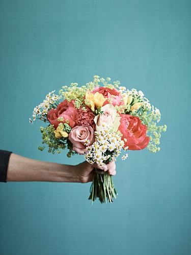 Hand hält Blumenstrauss aus Rosen, Pfingstrosen, Fresien und Kamillenblüten