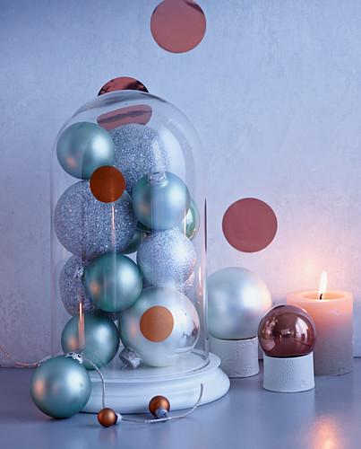 Silberne Christbaumkugeln unter Glassturz mit brennender Kerze