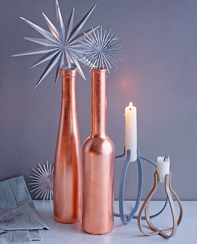 Christmas arrangement of silver stars, copper-coloured bottles and candles