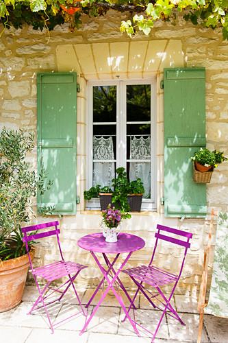 Sitzplatz mit violetten Gartenmöbeln vor französischem Steinhaus