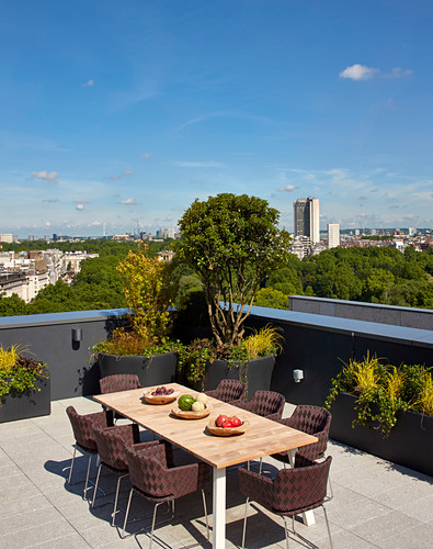 Brown chairs around dining table on roof terrace with view across London