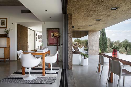 Essbereich mit Klassikerstühlen vor offener Terrassentür, Tisch mit Stühlen auf überdachter Terrasse