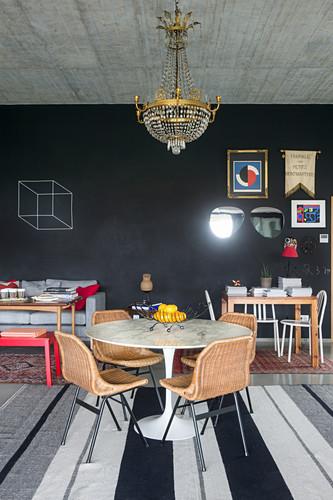 Runder Tisch mit Rattanstühlen unter Kronleuchter, im Hintergrund schwarze Tafelwand