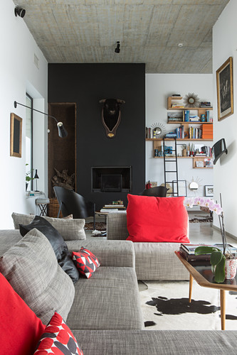 Grey sofa set with red scatter cushions in front of bull's head on black wall above fireplace