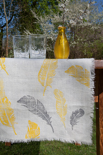 Table runner printed with yellow and grey feathers