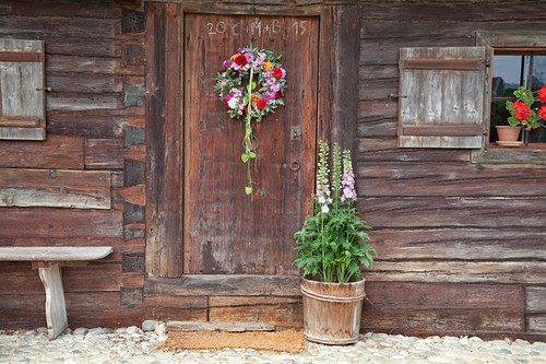 Door wreath of sage leaves, dahlias, phlox and green physalis husks and pot of snapdragons