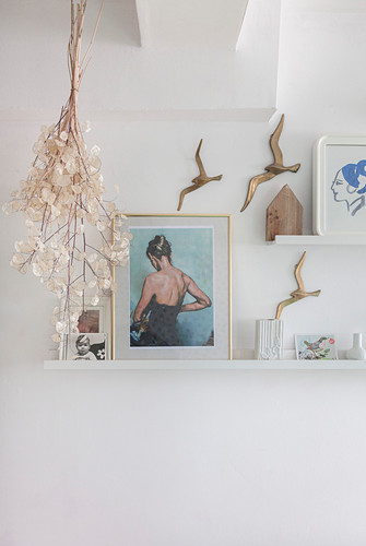 Pictures on shelves and bird ornaments on white walls