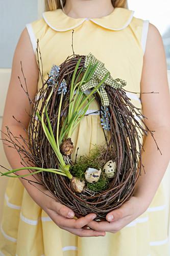 Mädchen hält eiförmigen Osterkranz mit Traubenhyazinthen und Wachteleiern
