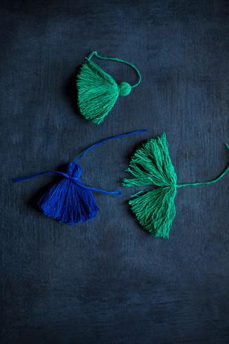 DIY-Quasten in Grün und Blau auf schwarzem Untergrund