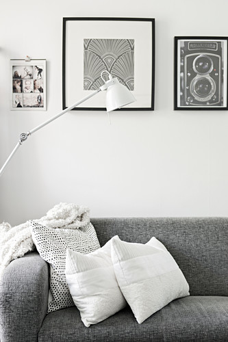 Cushions on grey sofa below black and white pictures and standard lamp