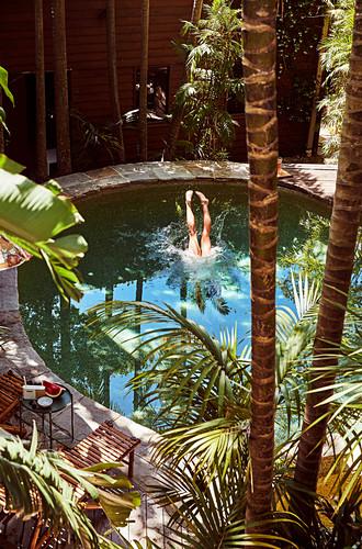 Blick auf Pool in exotischem Garten, Beine ragen aus dem Pool