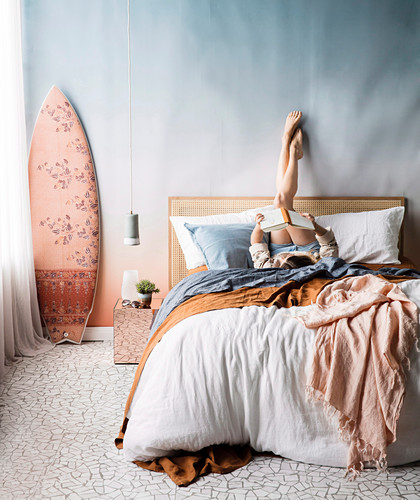 Pastel-colored bedroom, young woman on double bed, pendant lamp and surfboard next to it