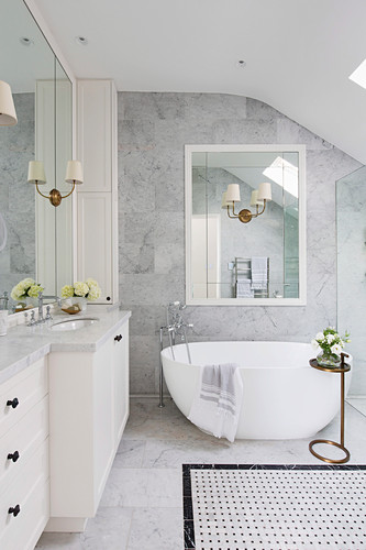 Bright bathroom with marble tiles and free-standing bathtub