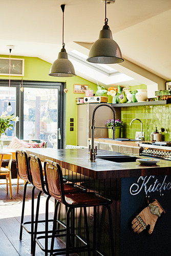 Island counter in kitchen-dining room with green walls