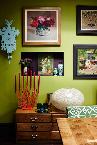 Ornaments in niche in green wall above chest of drawers