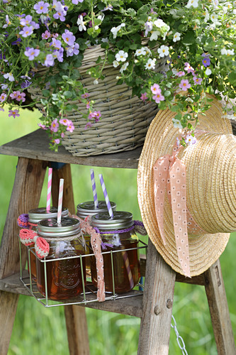 Drinks in screw-top jars, flowers and hat on ladder