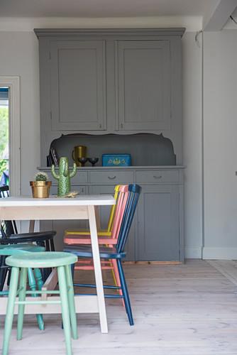 Tisch mit bunten Stühlen vor grauem Küchenbuffet