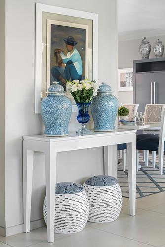 Symmetrisch angeordnete Deckelvasen auf Konsolentisch und passende Hocker darunter