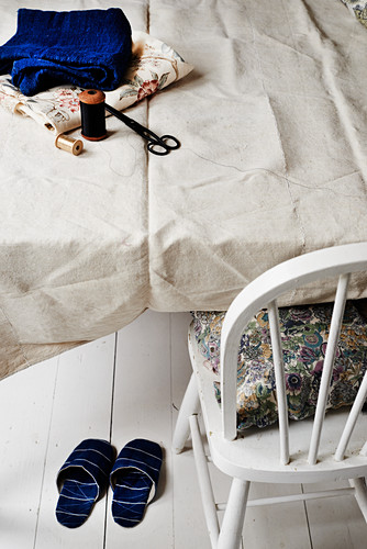 Hand-sewn slippers under sewing utensils on table