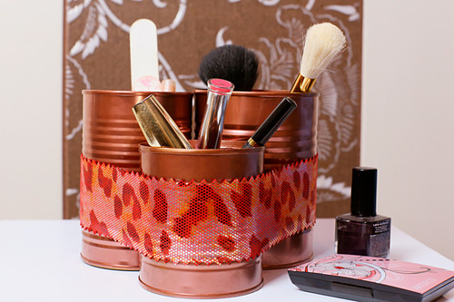 Makeup brushes in organiser made from painted tin cans