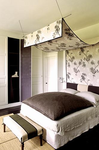 Geblümter Baldachin über dem Bett im Schlafzimmer mit Einbauschränken