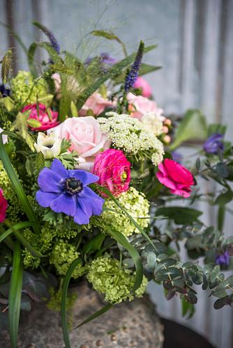 Bunter Frühlingsstrauß mit blauen, rosafarbenen und grünen Blumen