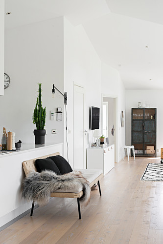 Fur blanket and cushions on bench against kitchen counter in open-plan interior