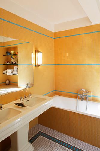 Vintage twin sinks, bathtub and mosaic tiles in bathroom