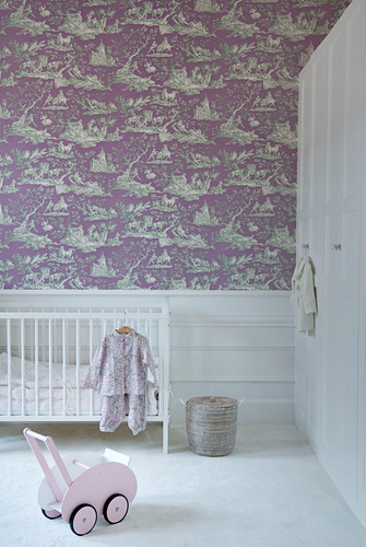 Cot against wall with purple toile de jouy wallpaper