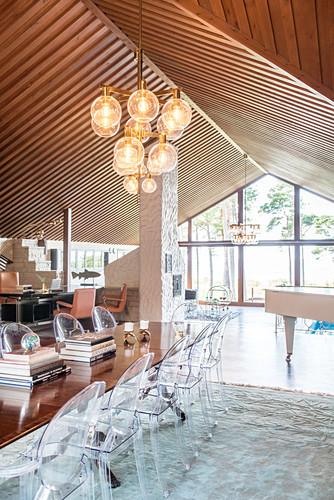 Transparente Designerstühle am langen Esstisch im Dachzimmer