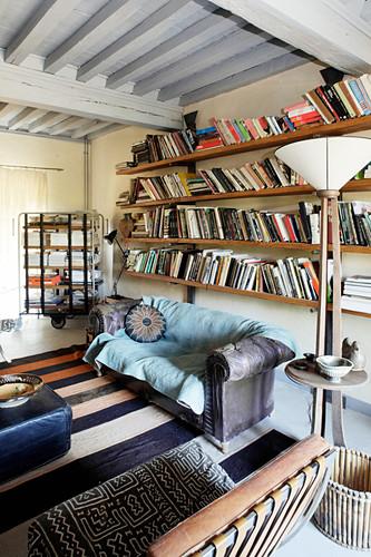 Old sofa below bookshelves in vintage-style living room