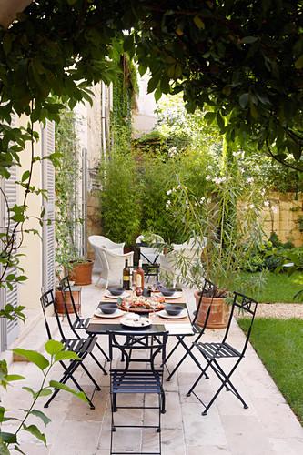Gedeckter Tisch und schwarze Gartenstühle auf der Terrasse