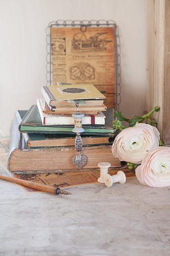 Lesezeichen mit Anhänger aus einer Garnrolle im Stapel alter Bücher