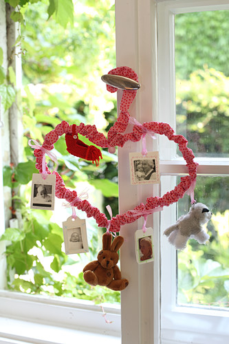 Mobile made from coat hanger bent into love heart and covered in red fabric