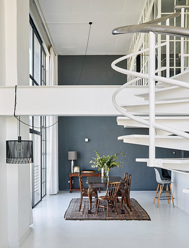Dining table and chairs next to glass wall in high-ceilinged room with white spiral staircase in foreground