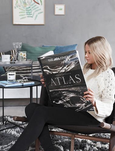 Frau sitzt im Wohnzimmer und schaut in einen Atlas