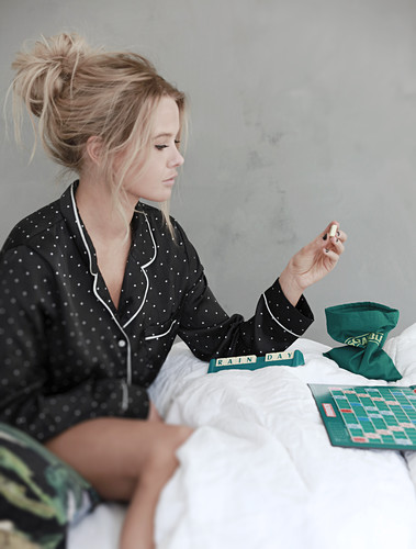 Young woman wearing pyjamas playing Scrabble in bed