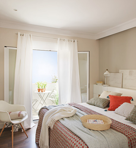 Bedroom in muted shades with open door leading to balcony