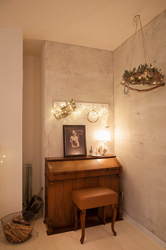 Piano and stool in corner of festively decorated room